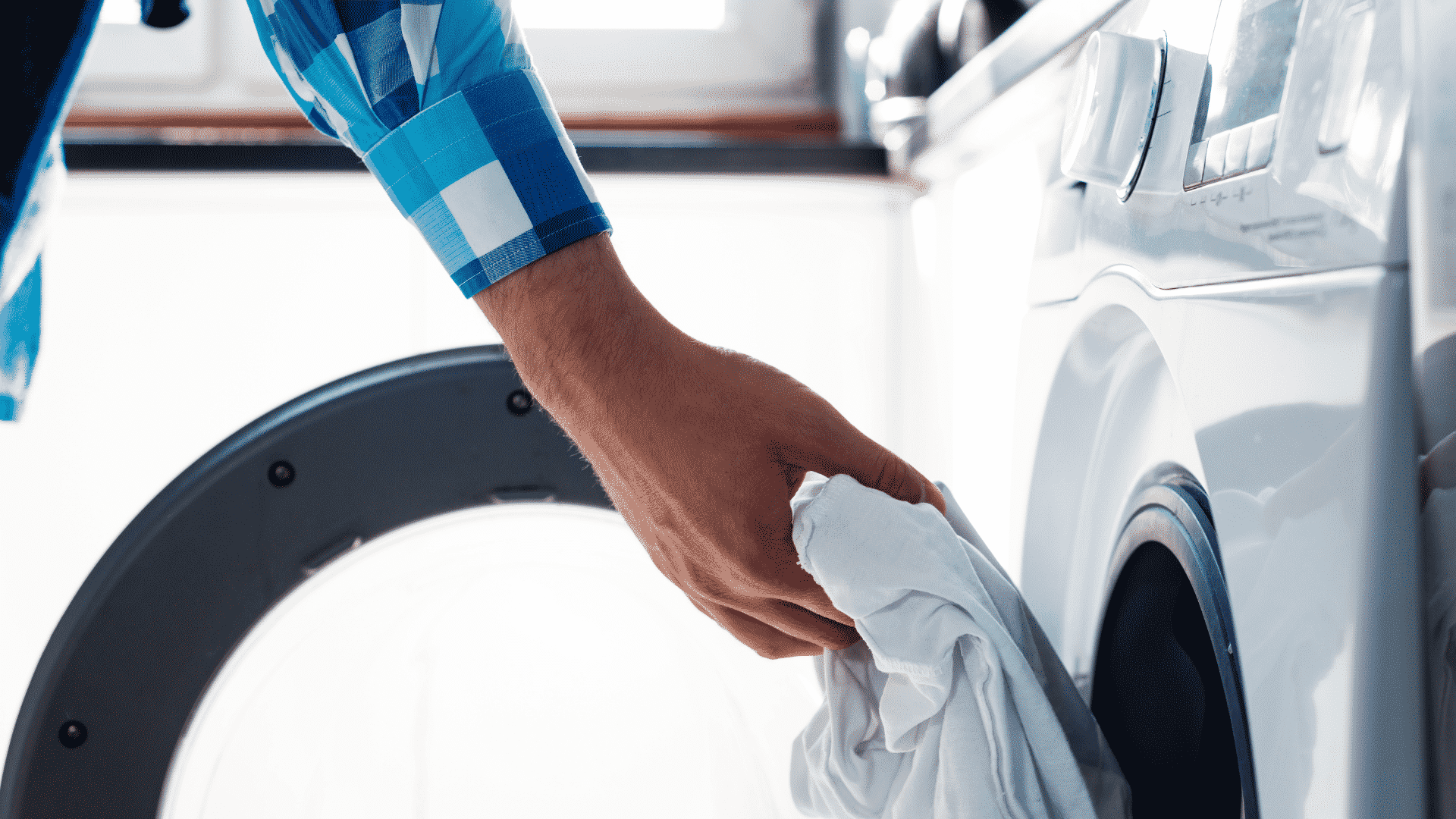 man puts clothes in dryer
