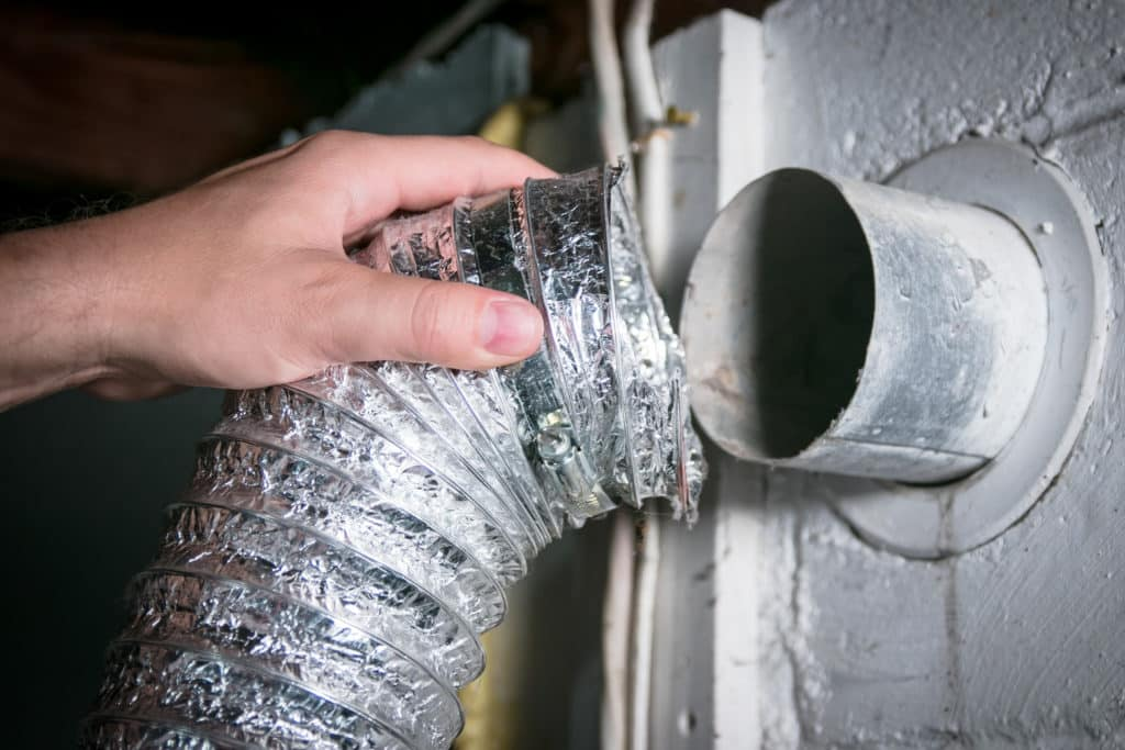 A Dallas dryer vent cleaning technician disconnects a flexible dryer vent hose from the wall.
