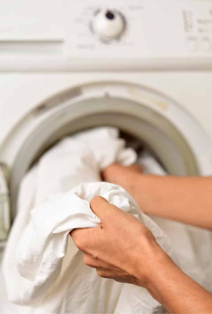 Dryer vent cleaning in Dallas. A person pulls white sheets from a dryer.